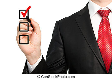 Isolated businessman in a suit with a red tie holding a pen and writing red check mark or make a choice