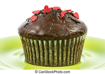 Isolated chocolate muffin on a green plate