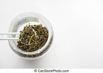 isolated close up scoop dried green tea leaf from plastic bottle