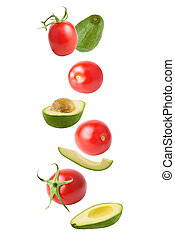 Tomato and avocado in the air isolated on white background with clipping path