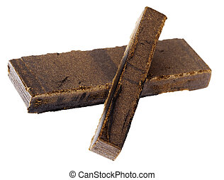 A 10 grams piece of Hashish laid on top of a 20 grams piece, isolated on white background. This pieces represent the quantity of three retail units.