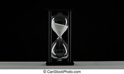 Isolated hourglass. Hourglass with white sand. Black - White...