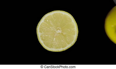 Isolated lemon cut with a knife in the studio on a black background