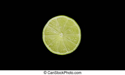 Isolated lime cut with a knife in the studio on a black background