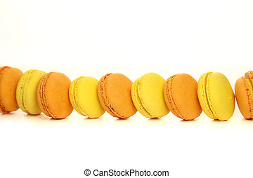 yellow and orange macaroons in a row on a white background