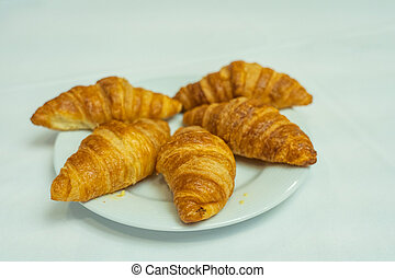 Isolated plate of puffy croissant on white plate for breakfast