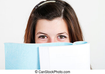 girl behind book - isolated pretty teen girl behind book