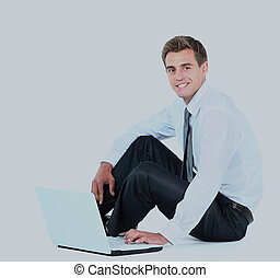 Isolated seated young businessman using a laptop.