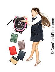Isolated shot of cute schoolgirl emptying backpack full of books