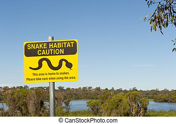 Yellow Snake warning sign in wetland park adjacent to residential area in the city of Perth, Western Australia, with blue sky as background and copy space.