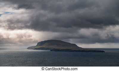 Isolated steep island time lapse with dark clouds - Time...