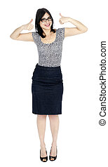 An adult (early 30's) black haired caucasian woman, wearing a dotted shirt and a dark jeans skirt looking at the camera with a toothy smile and her arms raised in thumbs up motion. She is very satisfied. Isolated on white background.