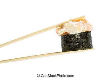 Isolated sushi gunkan in chopsticks. Macro.