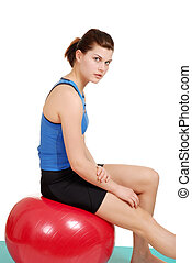 woman resting on red exercise ball