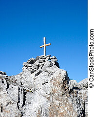 isolated wooden summit cross on a sharp and jagged mountain peak under a blue sky
