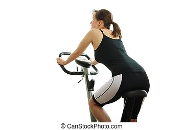 Isolated young woman riding on a spinning bicycle