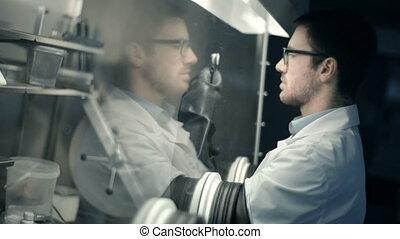 Isolation Glove Box - Laboratory technician using isolation...