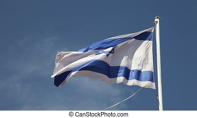 Israel flag waving in wind against blue sky