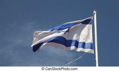 Israel flag waving in wind against blue sky