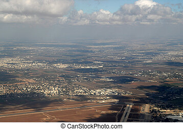 Israel from the height of airplane, city and road, oases in the desert a great land, clouds descending to the ground.