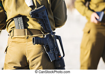 Israeli girl soldier with a gun, shot from the back.