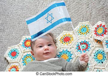 Israeli newborn baby holding the Israeli flag. - An Israeli...