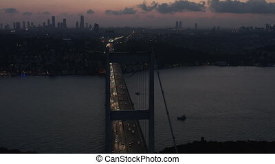 Istanbul 15 July Martyrs Bosphorus Bridge at Dusk or Night with City Skyline Silhouette and Car traffic flowing out of the City lights, Aerial slide right