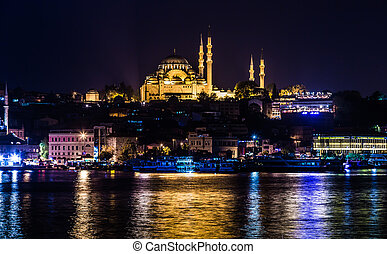 ISTANBUL - APRIL 30: Night view on the restaurants at the end of the Galata bridge, Sultanahmet, at sunset with the famous Suleymaniye Mosque in the background, Istanbul, Turkey, APRIL 30, 2013