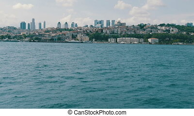Istanbul, Turkey - June 12, 2019: Rich luxury quarter of residential buildings on green hills by the sea that are surrounded by greenery against the background of large skyscrapers of business centers.