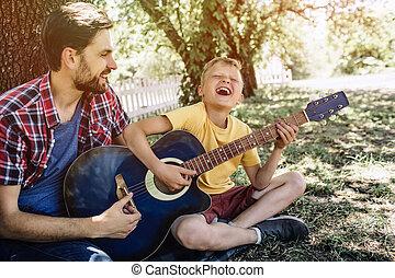 it., ギター, 目, 彼の, 助力, 保持, 男の子, 得意な父親, 満足させられた, son., 若い, him., 保有物, closed., 遊び, 歌うこと, うれしい, 彼