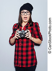 It can be a cool shot!  Surprised young woman in headwear and glasses holding camera and looking at camera while standing against grey background