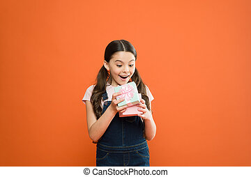 It caught her by surprise. Cute small child opening gift box with surprise face on orange background. Adorable little girl getting birthday surprise. Being shocked of pleasant surprise