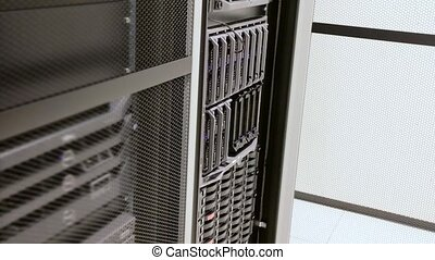 It engineer or consultant installing a blade server in data rack. Shot in enterprise datacenter.