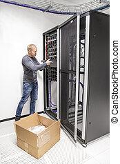 IT engineer installs network switch in datacenter - IT...