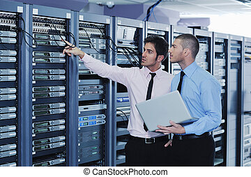 it engineers in network server room - group of young ...