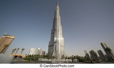 It is a calm summer day, in front of Burj Dubai and some other buildings there are fountains