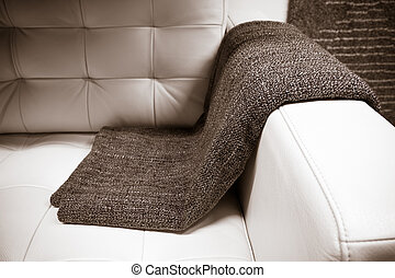 gray blanket draped over a leather couch - it is a gray...