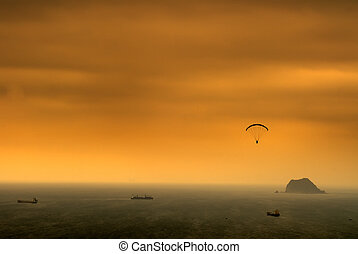 It is a kind of sport called parachuting over the sea.