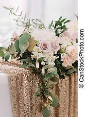 It is a lot of wedding flowers on a table with a golden cloth.