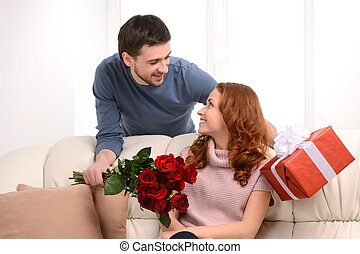 It is all for you! Handsome young men presenting a gift box and  a bunch of flowers to his attractive girlfriend
