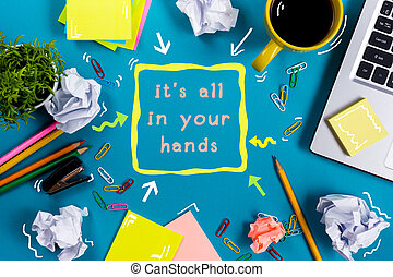 It is all in your hands. Office table desk with supplies, white blank note pad, cup, pen, pc, crumpled paper, flower on blue background. Top view
