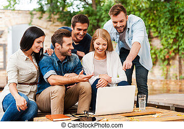 It is brilliant idea! Group of joyful young people looking at laptop while working together outdoors