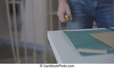 It is close-up image of man cutting paper with stationary knife