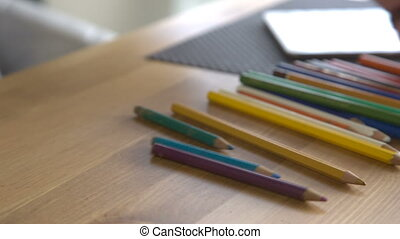 It is close-up image of woman putting colorful pencils on table
