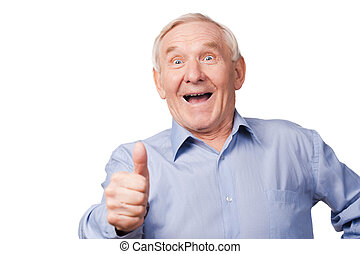 It is cool! Excited senior man stretching out his hand with thumb up while standing against white background