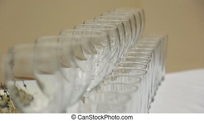 It is focusing view of glasses served in banquet table standing in row.