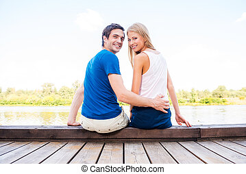 It is our first date. Beautiful young loving couple sitting at the quayside together and looking over shoulder with smile