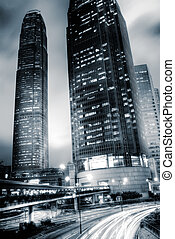 It is skyscraper with traffic light and cars motion blurred...