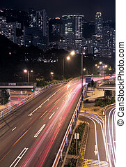 It is skyscraper with traffic light and cars motion blurred in Hong Kong.