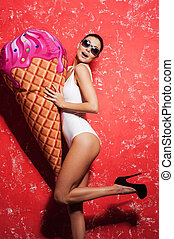 It is so big! Beautiful young woman in sunglasses and funky clothing holding huge fake ice cream while standing against red background